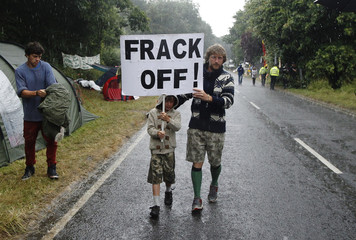 """A man and boy walk through the rain with a placard that reads """"Frack Off!"""" during a protest outside the village of Balcombe in southern England"""