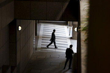A businessman smokes outside an office building as another walks past in Tokyo