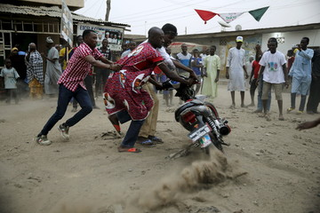 Supporters jubilate along a street after All Progressive Congress candidate Muhammadu Buhari is pronounced the winner of Nigeria's presidential election, in Kano