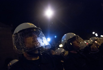 Police officers in riot gear stand guard in the rain as demonstrators protest in the streets during an anti-NATO protest march in Chicago