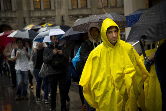 People line up to enter the Museum of Modern Art as heavy rain falls in New York