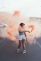young beautiful woman outdoor using colorful smoke bomb