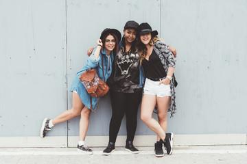 Three women friends outdoor hugging looking camera