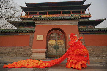 Chinese artist Kong Ning symbolically makes warning sounds in her costume made of hundreds of orange plastic blowing horns during her art performance raising awareness of the hazardous smog in front of the Drum tower in a historical part of Beijing