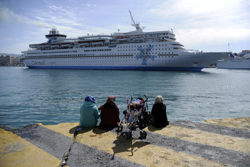 Stranded refugees and migrants watch a cruise ship leaving the port as they sit close to a shelter for refugees and migrants at the port of Piraeus, near Athens