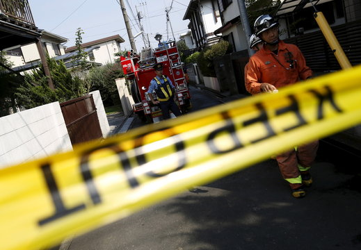 A police officer stands guard on the street in front of the site where a light plane went down in a residential area and burst into flames, in Chofu