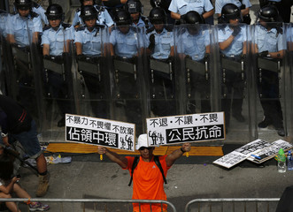 A protester holds up placards in front of a line of riot police outside government headquarters in Hong Kong