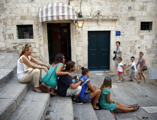 Tourists sit on stairs in Croatia's UNESCO protected medieval town of Dubrovnik