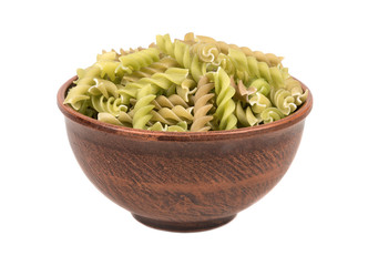Green pasta fusilli in a bowl on white background