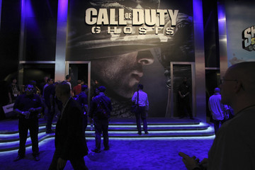 """People stand near the """"Call of Duty:Ghosts"""" game exhibit on the first day of E3, the Electronic Entertainment Expo, in Los Angeles"""