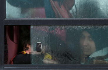 A displaced woman and a child are seen through a window on a bus as they flee the Islamic State stronghold in the town of Bartella, east of Mosul