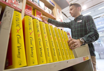A shop worker stacks shelves with the first copies of author J K Rowling's first adult fiction book The Casual Vacancy as it goes on sale at a bookshop in central London