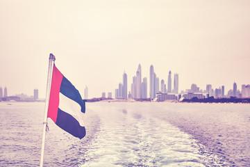 Vintage stylized  United Arab Emirates flag with Dubai skyline in distance, selective focus.