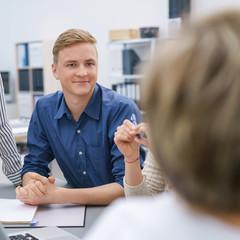 junger mann im büro hört seiner kollegin zu in einer besprechung