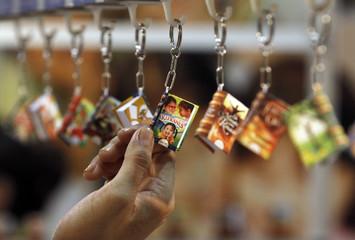 A Salvadoran touches a miniature book at the XV International Book Fair of Central America, in San Salvador