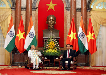 India's Prime Minister Narendra Modi and Vietnam's President Tran Dai Quang talk under a statue of late Vietnamese revolutionary leader Ho Chi Minh at the Presidential Palace in Hanoi, Vietnam