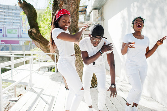 Three stylish african american friends, wear on white clothes. Street fashion of young black people. Black man with two african girls dancing gangsta rap style.
