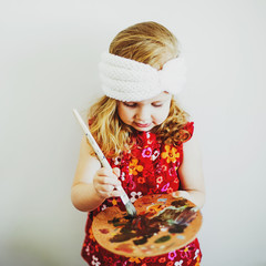 portrait of a little girl with an easel and paints, creating a painting