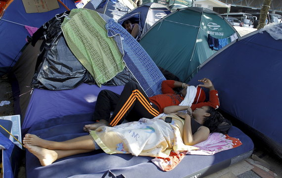 A couple of Cuban migrants sleep on an inflatable mattress at a makeshift camp at a border post with Panama in Paso Canoas