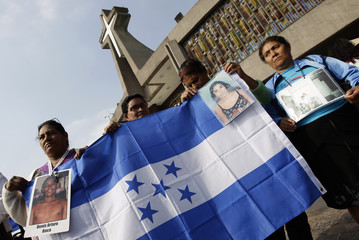 Central American women hold a Honduran flag with pictures of their relatives, who disappeared during their journey through Mexico to reach the U.S., as they arrive to attend a mass in Mexico City