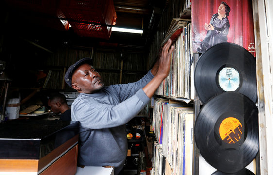 Vendor Rugami arranges vinyl records in his second-hand vinyl record stall at the Kenyatta Market in Nairobi