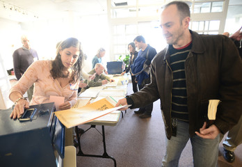 Election judge Sarro watches Jacobson, the first voter of the morning, slide his ballot into the box at the Boulder Library during the U.S. presidential election in Boulder