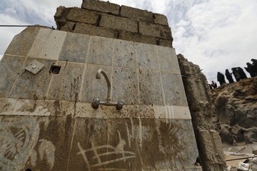 A tap is seen on an intact kitchen wall of a house destroyed by a Saudi-led air strike in Yemen's capital Sanaa