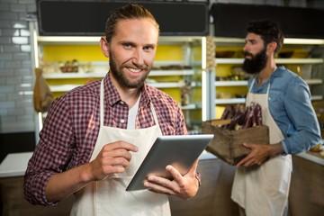 Portrait of smiling staff using digital tablet