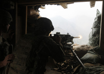 A U.S. soldier fires his machine gun from a bunker to the Taliban position in Ghaziabad district at Out Post Bari Alai in Kunar