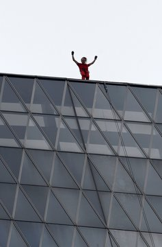 French climber Alain Robert, rock climber who has become famous for climbing known buildings worldwide waves after reaching top of the 215 metres high, 50 floors Bakrie Tower building in Jakarta