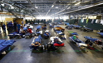 Migrants rest on folding beds in a former newspaper printing house used as a refugee registration centre for the German state of Hesse in Neu-Isenburg