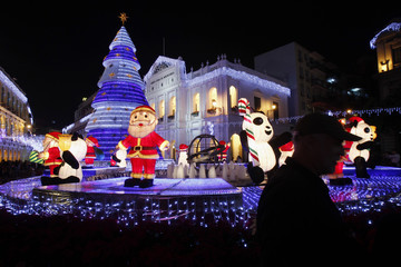 Man stands in front of Christmas decorations at Largo do Senado, the centre square in Macau