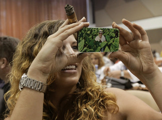 Cigar enthusiast from San Diego, California, takes a picture at a rolling lesson during the 15th annual Havana Cigar Festival