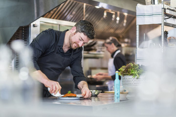 Chef garnishing food while female coworker working in background at restaurant