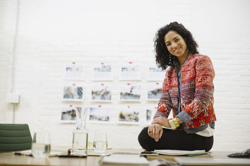 Portrait of smiling businesswoman sitting on table in office