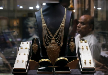 A gold necklace is displayed as a salesman waits for customers inside a jewelry showroom in the old quarters of Delhi