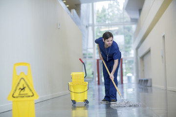 Male worker cleaning floor at hospital corridor Wall mural