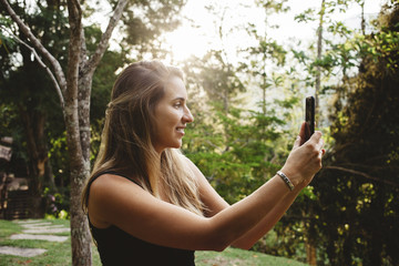 Smiling woman taking selfie while standing in yard