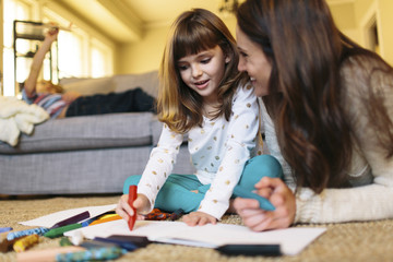 Mother looking at girl drawing on paper