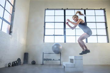Female athlete jumping on wooden seat in gym