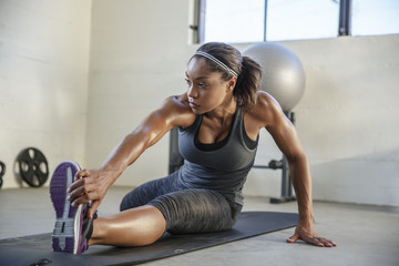 Female athlete stretching legs on exercise mat in health club
