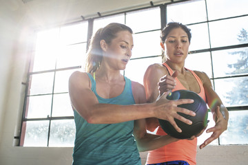 Friends exercising with medicine ball by window in gym
