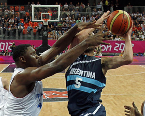 France's Seraphin tries to block the shot of Argentina's Ginobili during their men's preliminary round Group A basketball match at the Basketball Arena during the London 2012 Olympic Games