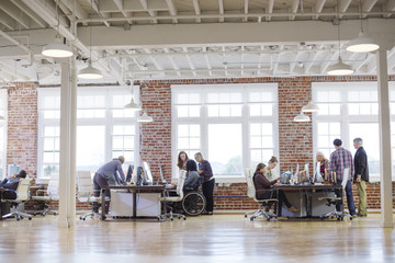Entrepreneurs working at desks by window in office