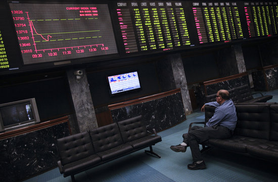 A man sits on a couch as he monitors share prices during a trading session at the Karachi Stock Exchange