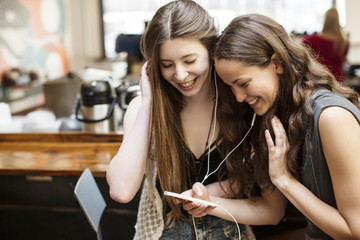Smiling friends using smartphone while sitting in cafe