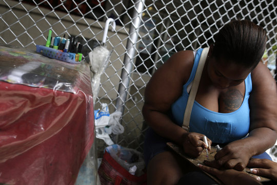 A street nail technician works on a client's manicure in Panama City