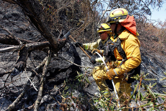 Firefighters use an axe to extinguish hotspots during the Soberanes Fire in the mountains above Carmel Highlands