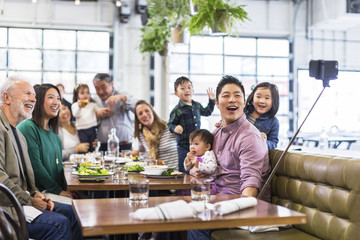 Happy multigenerational family taking selfie in restaurant