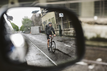 Male commuter riding bicycle on wet street seen through side-view mirror of car